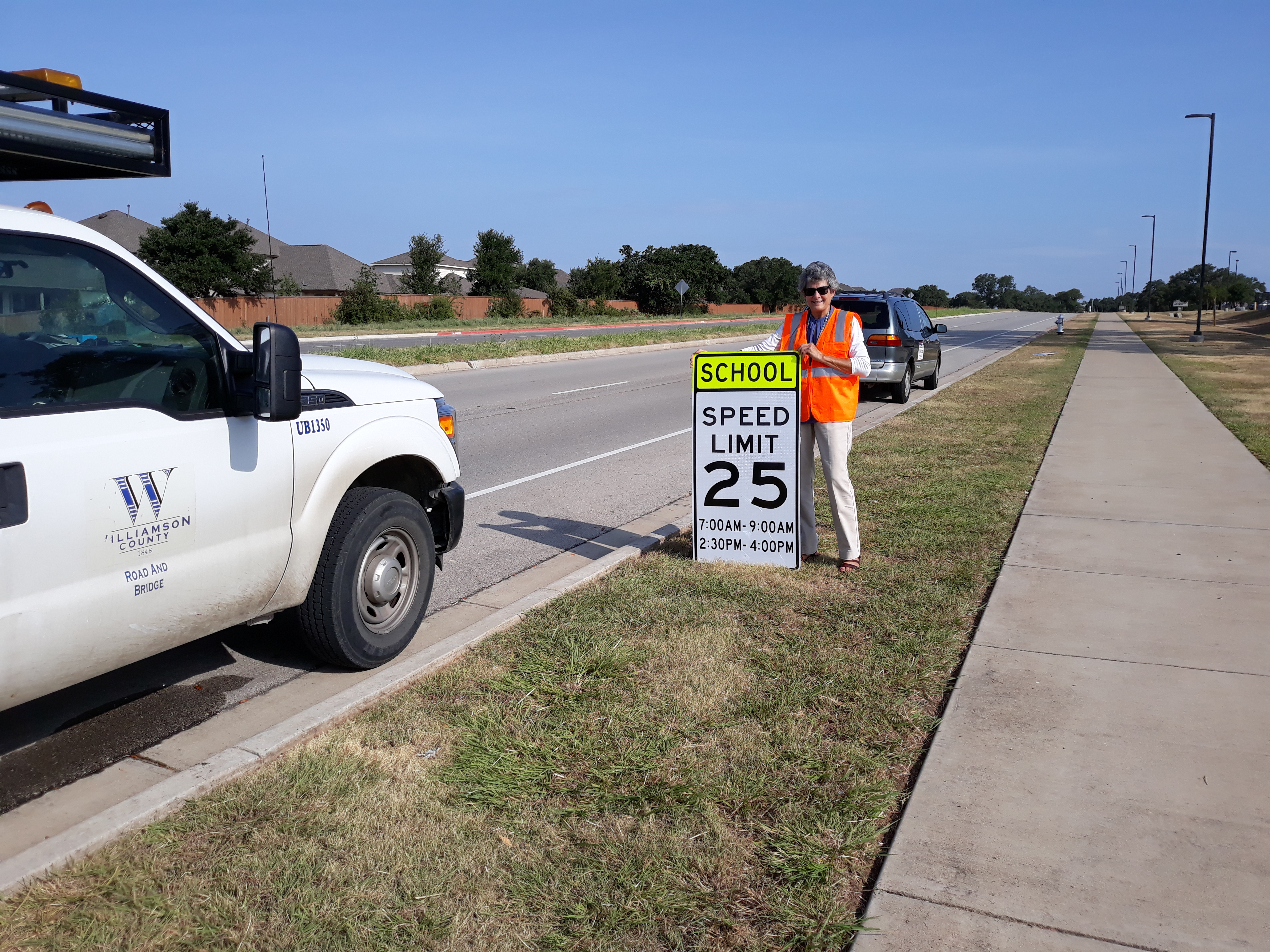 Commissioner Cook, wearing an orange vest, holds up a School Speed Limit 25 sign on Pearson Ranch Road.